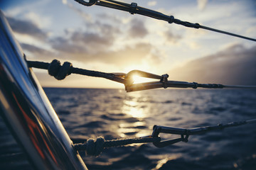 Close-up of railing in boat against sea during sunset