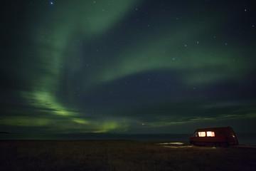 Illuminated van parked at sea shore against Aurora Borealis