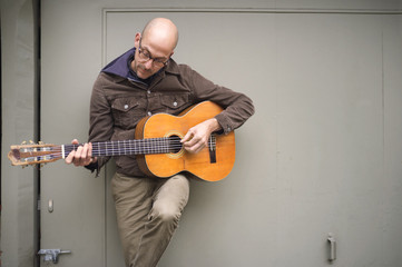 Man playing guitar while leaning on door