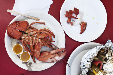 Overhead view of roasted lobster and salad served on red table