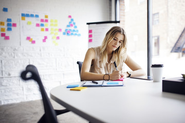 Businesswoman writing on adhesive note at table in office