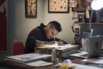 Male tattoo artist drawing on paper in studio