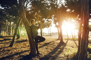 Jogger drinking water while leaning on tree in park at morning