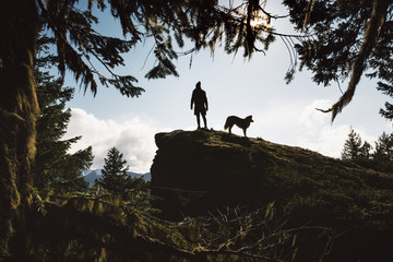Low angle view of silhouette man with dog standing on mountain against sky