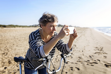 Woman taking picture through smartphone on beach