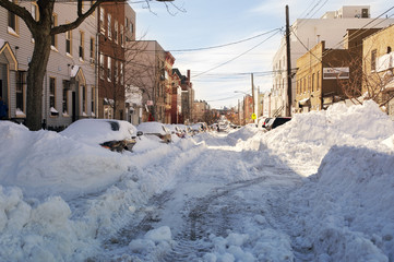 Cars on snow covered road amidst buildings in city