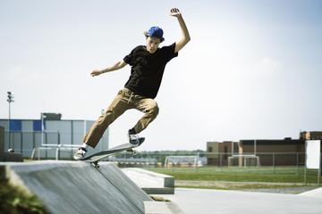 Young man performing stunts on skateboard