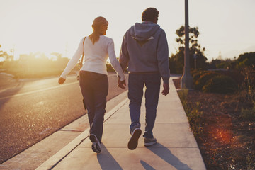 Rear view of couple walking on sidewalk on sunny day