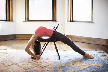 Woman stretching on chair at home