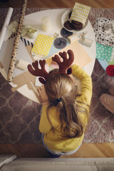 Overhead view of girl drawing at home during Christmas