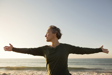 Senior woman with arms outstretched standing on beach against clear sky