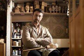 Portrait of confident craftsman sitting in workshop