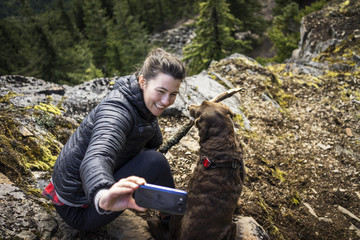 Smiling young woman talking selfie with dog on mountain