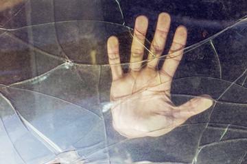 Close-up of hand on broken car window