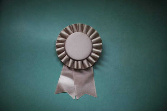 Close-up of award ribbon against green background