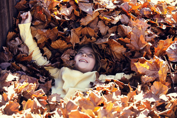 High angle view of girl lying on autumn leaves at field