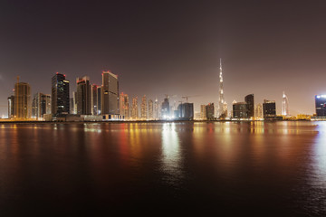 Illuminated cityscape and Dubai creek against clear sky at dusk