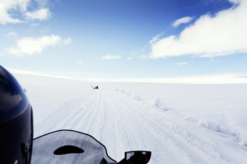 Cropped image of person riding snowmobile on landscape against sky