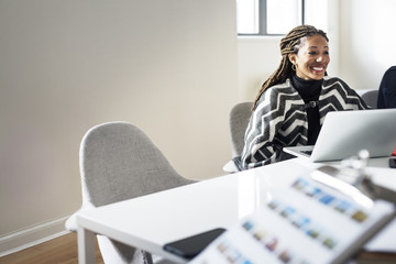 Smiling businesswoman with laptop sitting in office