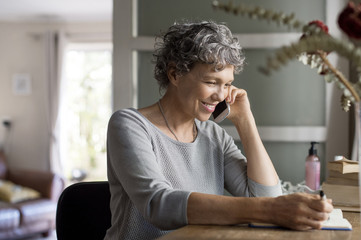 Mature woman talking on smart phone and writing in book at home