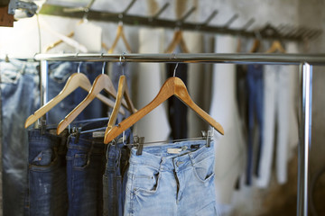 Various jeans hanging on coathangers at workshop