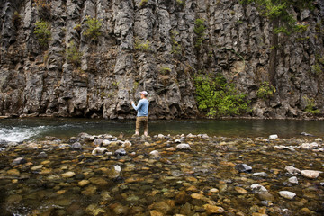 Rear view of man fly fishing at river against rock formations