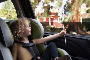 Boy playing with pinwheel while travelling by car