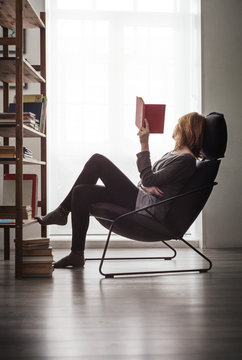 Woman holding book and relaxing on chair against window at home