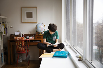 Boy using tablet while sitting by window at home