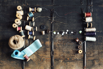 Overhead view of sewing equipment with thread reels on wooden table
