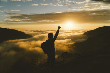 Silhouette female hiker gesturing while standing on mountain during sunset
