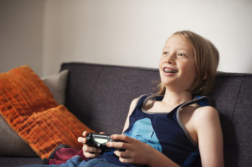 Smiling girl playing video game while sitting on sofa at home