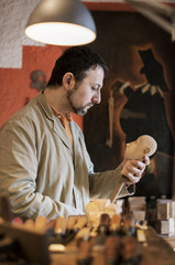Man making wooden figurine in workshop