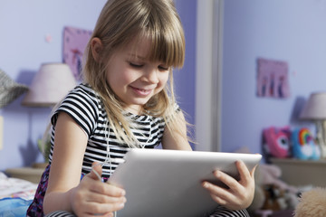 Low angle view of happy girl using digital tablet in bedroom