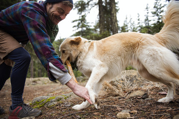 Happy man playing with dog in forest