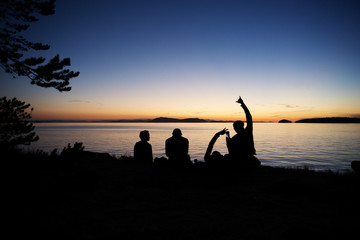 Silhouette men enjoying at Sucia Island against sky during sunset
