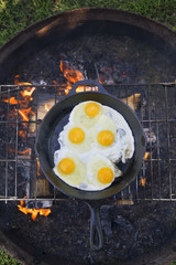 Overhead view of eggs being fried on campsite grill