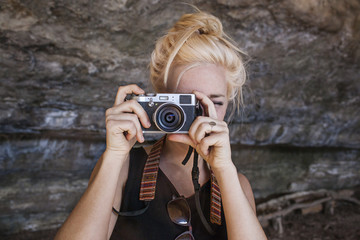 Young woman photographing through vintage camera against rock