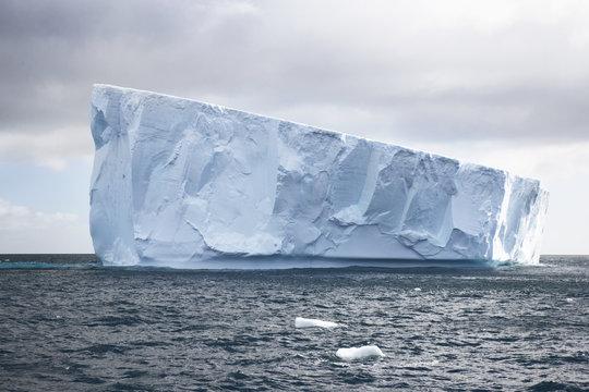 Glacier floating in sea against sky