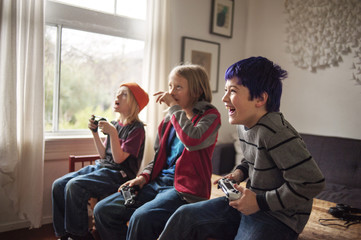 Smiling boys playing video games at home