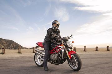 Portrait of Biker sitting on motorcycle wearing helmet