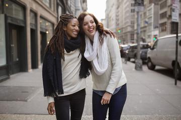 Smiling female friends enjoying on footpath