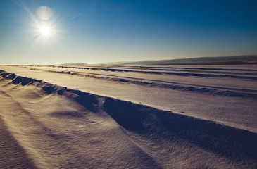Scenic view of snow covered landscape against sky on sunny day