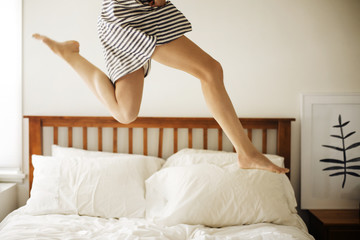 Low section of woman jumping in bedroom