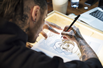 Photo Young Tattoo Artist Drawing On Table In Studio