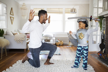 Father and son playing with sword at home