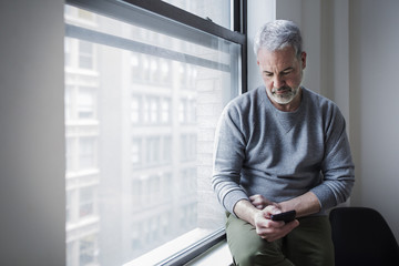 Mature man using smart phone while sitting on window sill at home