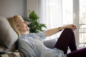 Side view of relaxed woman listening music while sitting on sofa at home