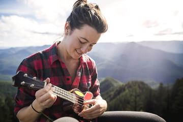 Happy woman playing ukelele against mountain range