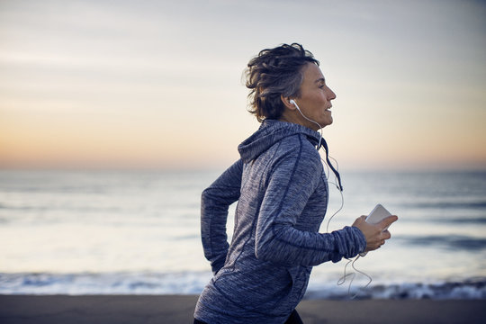 Woman running and listening to music on beach